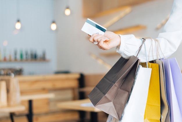 Mão de colheita com sacos de papel e cartão de crédito