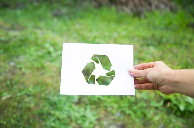 Mão de colheita com símbolo de reciclagem