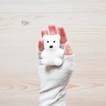 Mão de colheita com urso de brinquedo