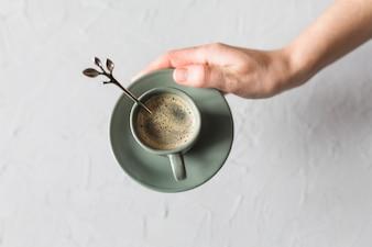 Mão de colheita com xícara de café e pires