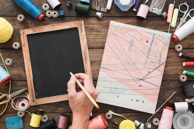 Mão de colheita de desenho no quadro-negro perto de material de costura