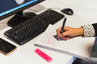 Mão de colheita escrevendo no caderno perto de computador