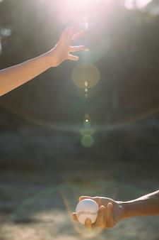 Mão de colheita jogando beisebol para outra mão
