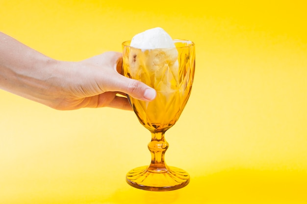 Mão de colheita segurando a taça de sorvete