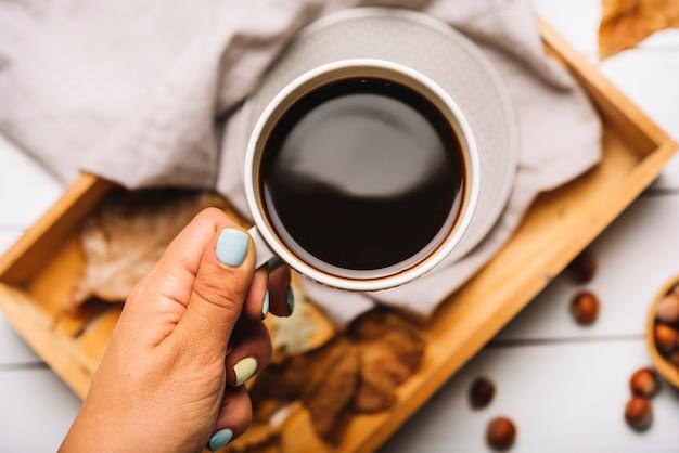 Mão de colheita segurando café sobre bandeja
