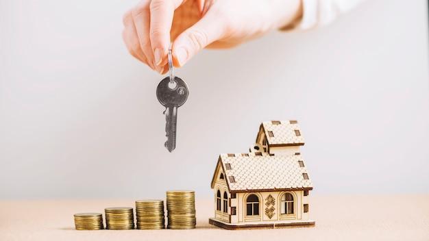 Mão de colheita segurando chave perto de casa e dinheiro