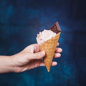 Mão de colheita segurando o cone com sorvete