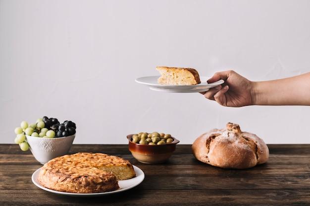 Mão de colheita segurando saboroso bolo sobre a mesa