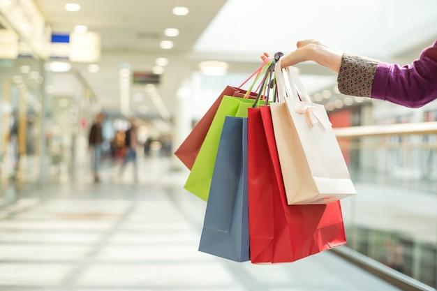 Mão de colheita segurando sacolas de compras