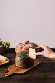 Mão de colheita, tomando o pedaço de queijo