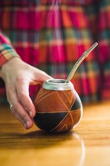 Mão de colheita tomando yerba mate cup