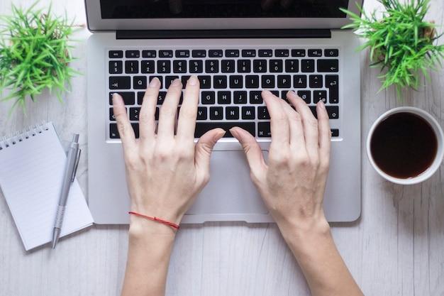 Mão de colheita usando laptop perto de café e notebook