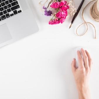 Mão de colheita usando o mouse perto de laptop e buquê