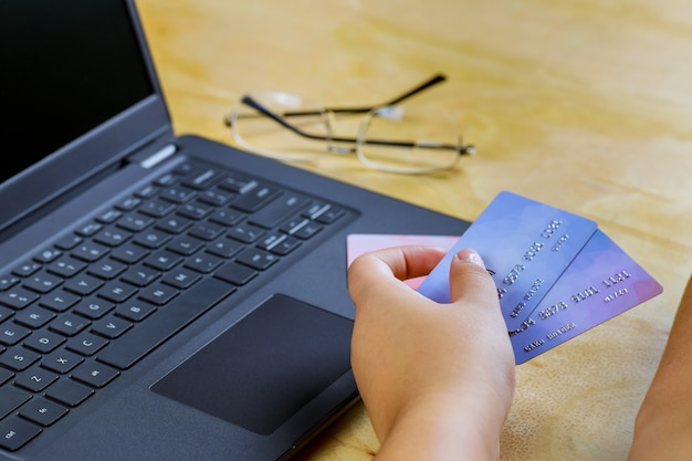 Mão de comércio eletrônico segurando um cartão de crédito usando um laptop e gastando dinheiro em compras on-line no internet banking