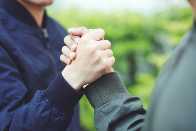 Mão de companhia segurando confiança de sucesso, conceito confiante. ou close de uma mão de negócios entre dois colegas em parques.