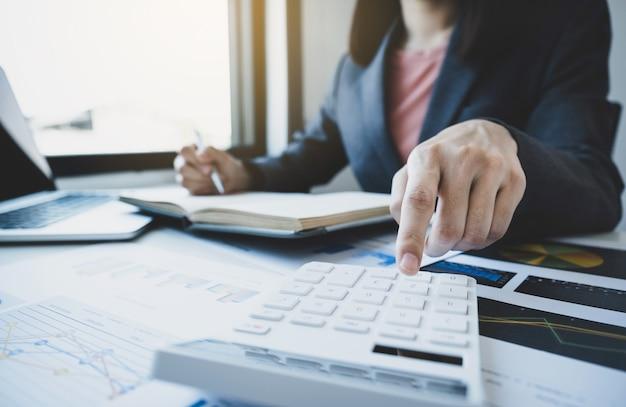 Mão de contadora de mulheres de negócios usar calculadora e laptop fazendo conta para pagar impostos na mesa branca no escritório de trabalho.