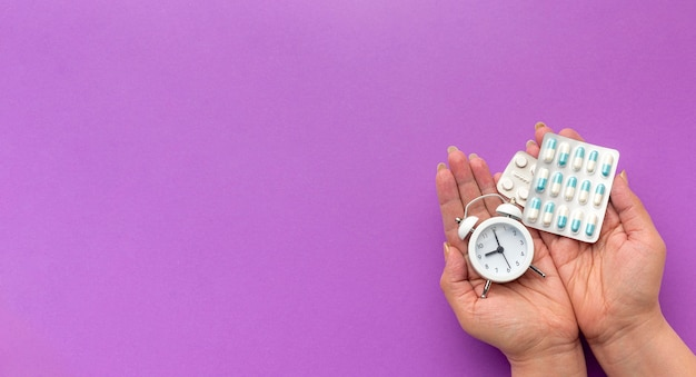 Mão de cópia-espaço com relógio e pílulas