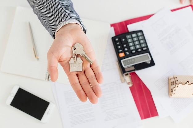 Mão de corretor de imóveis com chaves