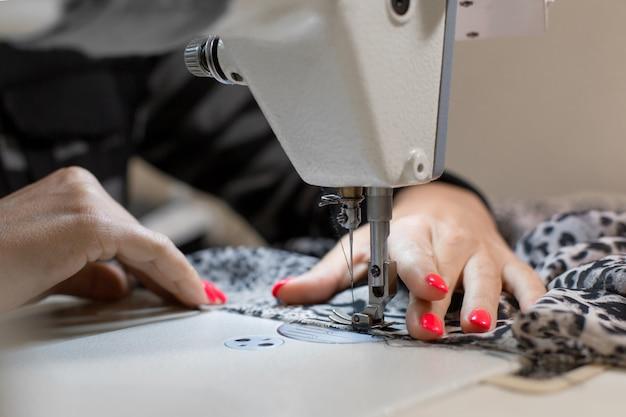 Mão de costureira de close-up costura máquina de costura de tecido