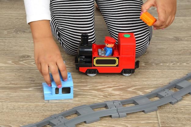 Mão de criança brincando com a ferrovia infantil