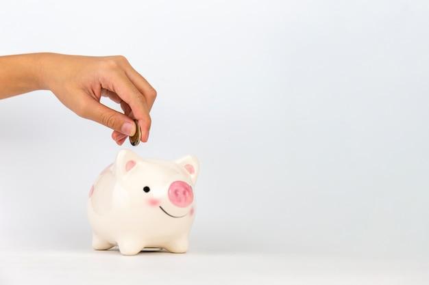 Mão de criança colocando moedas no cofrinho em fundo branco