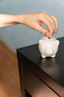 Mão de criança colocando uma moeda em um cofrinho. conceito de ganhos, economia e finanças.