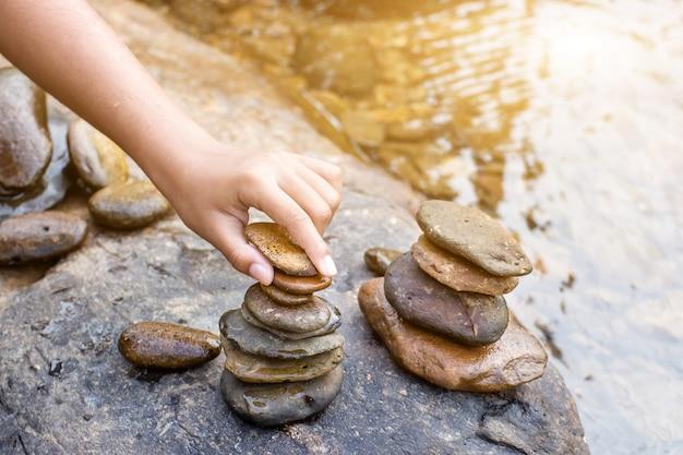 Mão de criança colocando uma pilha de pedras em cima de um monte de pedras no riacho, fundo desfocado.