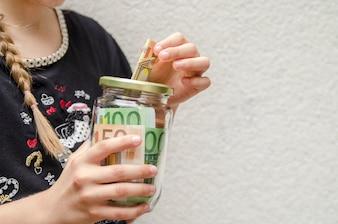 Mão de criança colocar dinheiro no pote de vidro para salvar ou doar dinheiro