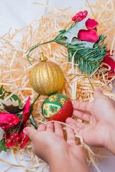 Mão de criança com bolas para decoração de natal em fundo de palha no rio de janeiro.
