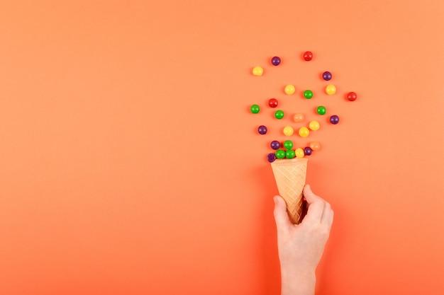 Mão de criança com cone de waffle e doce drageia