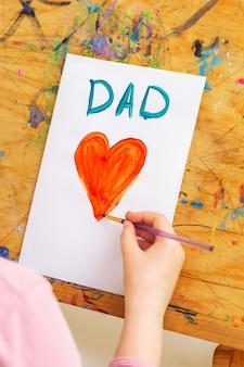 Mão de criança desenhando um coração vermelho com a palavra papai cartão em papel branco em um cavalete. família e o conceito de dia dos pais.
