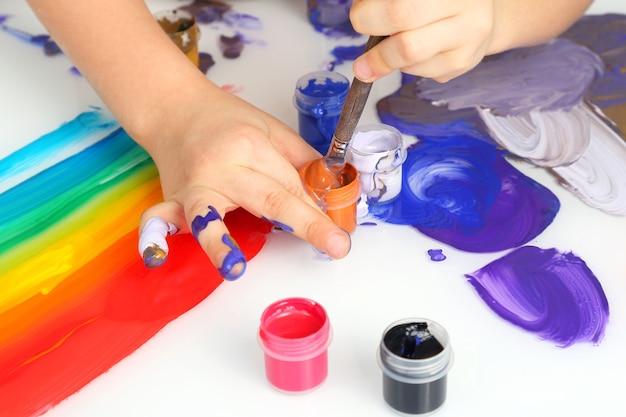 Mão de criança desenhar cores de pintura