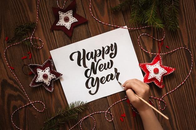 Mão de criança escreve feliz ano novo, letras.