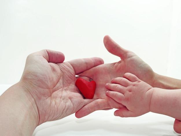 Mão de criança, mãe e pai com coração feito de play clay
