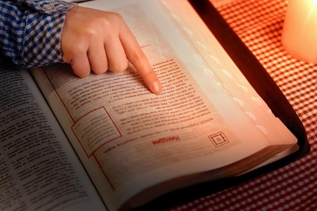 Mão de criança no livro do evangelho. dedo da criança apontando para o texto. lendo outro capítulo. estudando textos religiosos.