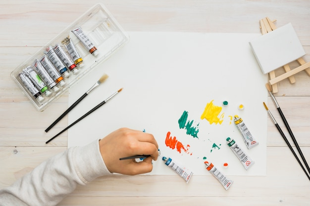 Mão de criança pintando em papel branco com pincel sobre a mesa de madeira