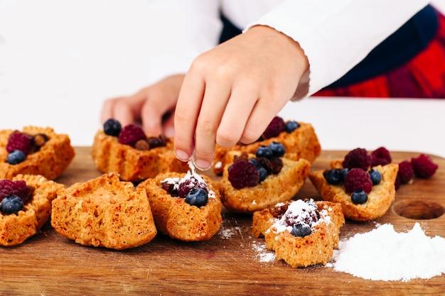 Mão de criança recheada de bolos com frutas frescas