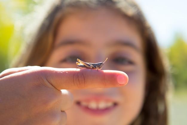 Mão de criança segurando o macro de bug de gafanhoto