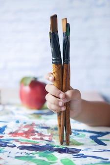 Mão de criança segurando um pincel artístico em um papel
