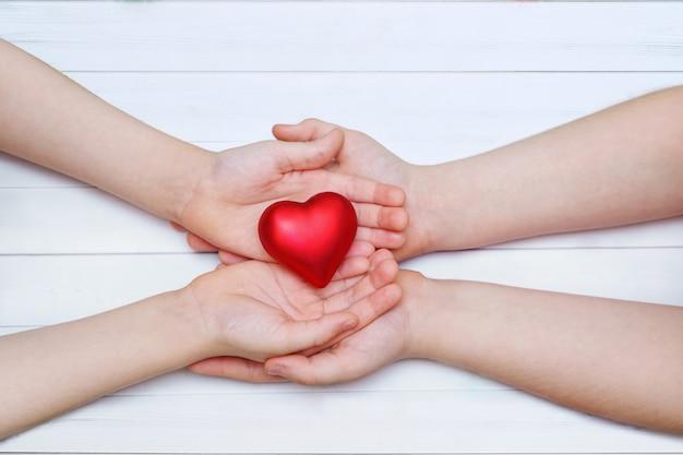Mão de crianças com coração vermelho.