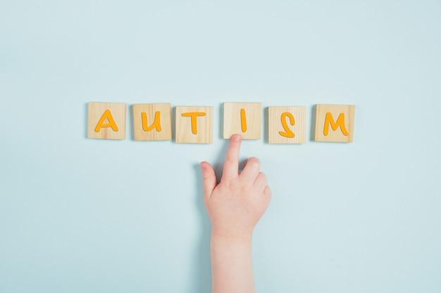 Mão de crianças e autismo em quadrados de madeira, vista superior de fundo azul