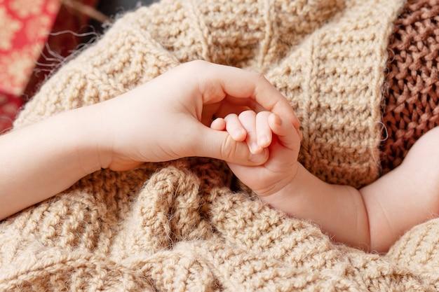 Mão de crianças recém-nascidas na mão do irmão. conceito de família feliz.