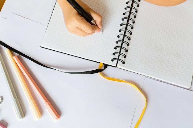 Mão de crianças segurando a caneta e escrever no caderno.