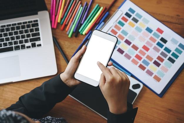 Mão de designer criativa feminina usando smartphone na mesa de design criativa. telefone móvel de tela em branco