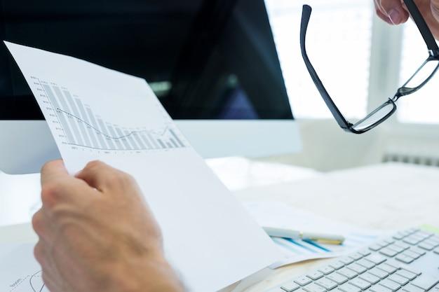 Mão de documento de gráfico masculina designer gráfico segurando