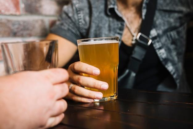 Mão de dois amigos segurando copo de bebidas alcoólicas