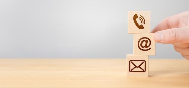 Mão de empilhamento de blocos de madeira com telefone celular de ícones, telefone de envelope de e-mail e endereço de e-mail contra fundo cinza. cubos de madeira com símbolo de telefone, e-mail, endereço. contate-nos