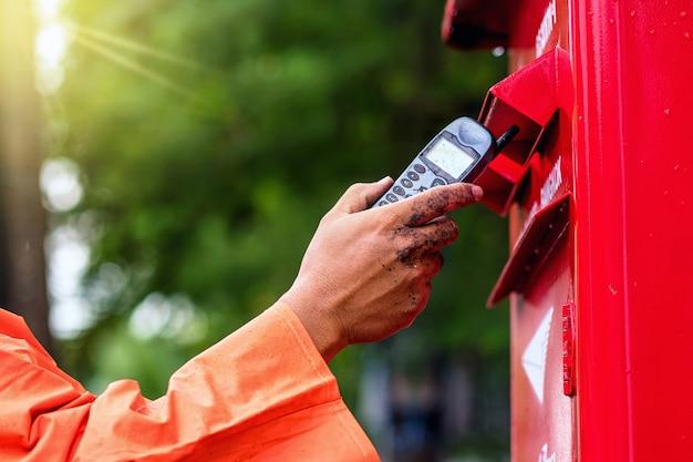 Mão de empregada segurando o velho móvel e colocar em caixa postal