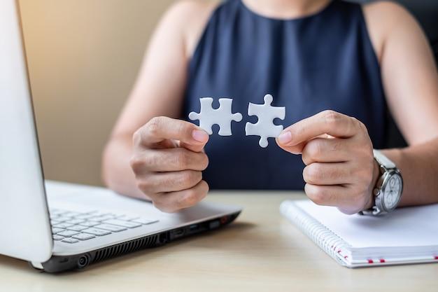 Mão de empresária conectando peça de quebra-cabeça de casal