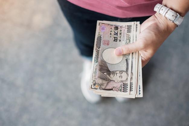 Mão de empresária segurando a pilha de notas de ienes japoneses. conceitos de negócios, dinheiro, investimento, finanças e pagamento